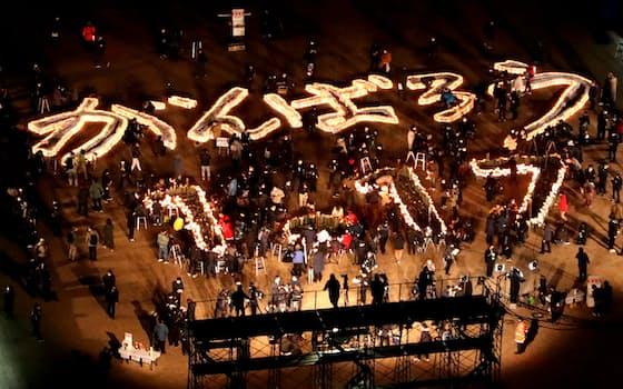阪神大震災から26年で、追悼会場に灯籠の明かりで浮かび上がった「がんばろう 1・17」の文字(17日、神戸市中央区)