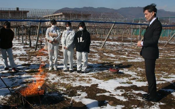 炭化器を使って剪定枝を燃焼させると炎が大きくなり煙は少なくなる(1月14日、山梨県笛吹市の笛吹高校付属農場、右は坂内啓二農政部長)