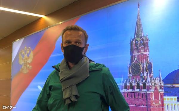 飛行機を降りた直後に空港で記者団の質問に応じたナワリヌイ氏(17日、モスクワ郊外)=ロイター