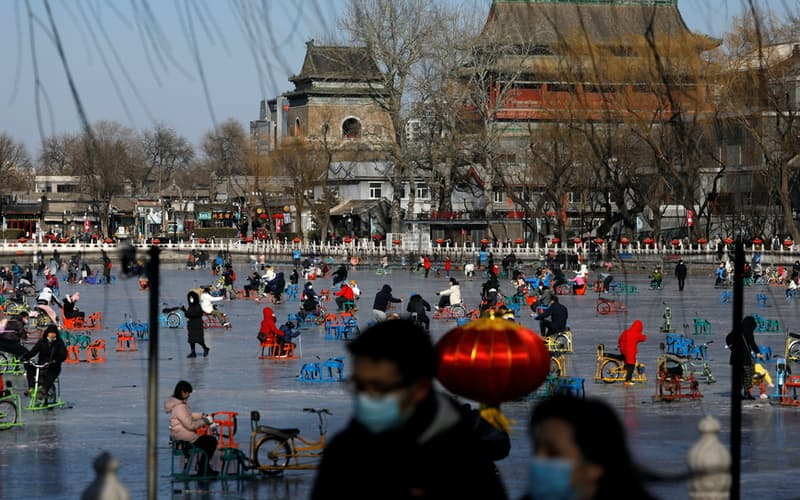 People wearing face masks following the coronavirus disease (COVID-19) outbreak skate on a frozen lake which has been turned to an ice rink, in Beijing, China January 16, 2021. Picture taken January 16, 2021. REUTERS/Tingshu Wang