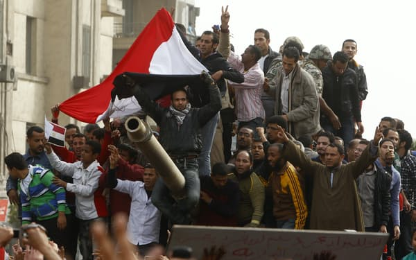 10年前は民主化の熱気にあふれていた(2011年1月、カイロで軍の戦車に上るデモ参加者)=ロイター