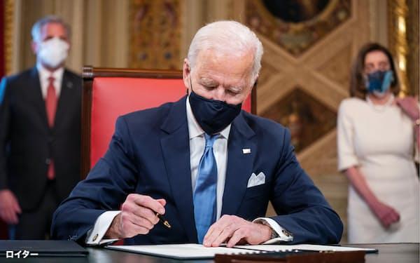 20日、大統領就任式を終え連邦議会議事堂の大統領執務室で文書に署名するバイデン氏=ロイター