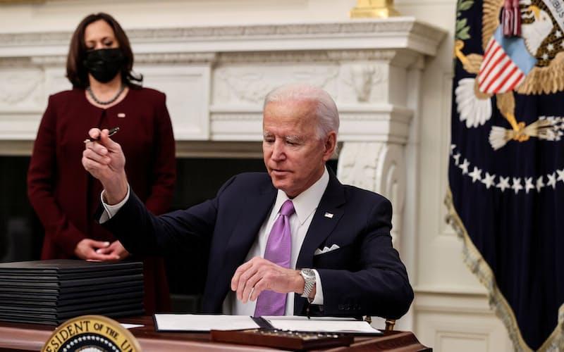 バイデン氏は21日、ホワイトハウスで10本のコロナ対策に関する大統領令に署名した=ロイター