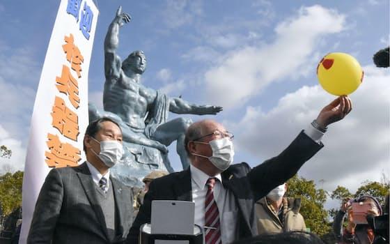 核兵器禁止条約の発効を受け、平和祈念像前で開かれた記念集会で、核弾頭を無力化して解体するイメージを込めて風船をしぼませる参加者(22日午前、長崎市の平和公園)=共同