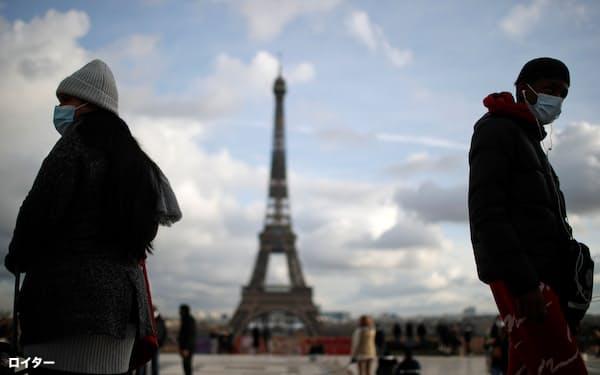 22日、マスクをしてパリ市内を歩く人々=ロイター