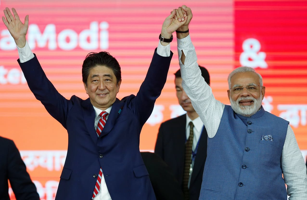 2017年9月、インドを訪問し、モディ首相と手を挙げる安倍前首相(左)=ロイター