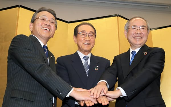 記者会見で握手する(右から)キリンホールディングスの磯崎社長、ファンケルの池森会長(当時)と島田社長(19年8月、東京都中央区)