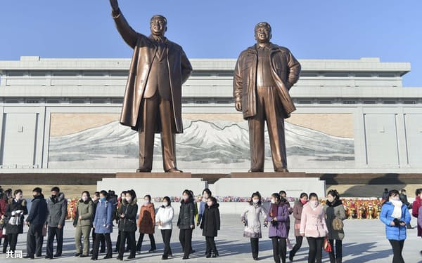 新年を迎え、故金日成主席(左)と故金正日総書記の銅像が立つ万寿台の丘に献花に訪れた市民ら(1月1日、平壌)=共同