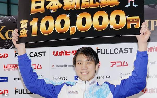 男子200メートル自由形を1分45秒13の日本新で制し、賞金ボードを掲げる松元克央