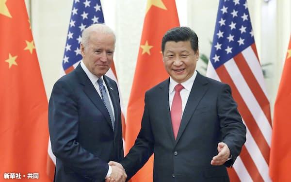 2013年12月、北京の人民大会堂で中国の習近平国家主席(右)と握手するバイデン米副大統領(当時)=新華社・共同