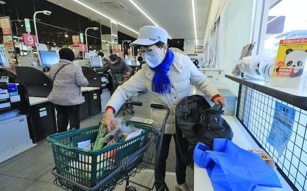 持参したマイ バッグに購入した商品を詰める買い物客(東京都練馬区のいなげや練馬関町店)