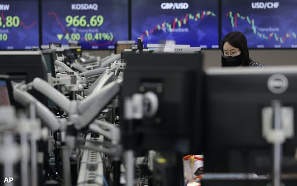 An employee of a bank watches computer monitors at the foreign exchange dealing room in Seoul, South Korea, Thursday, Feb. 4, 2021. Asian shares mostly fell Thursday as caution set in over company earnings reports, recent choppy trading in technology stocks and prospects for more economic stimulus for a world battling a pandemic. (AP Photo/Lee Jin-man)