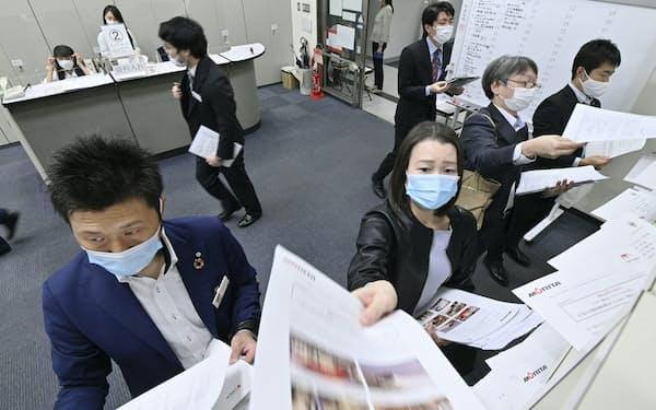 マスク姿で決算資料を投函する企業の関係者(東京証券取引所)
