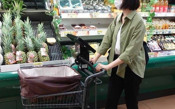 レジカート利用率が目標の20%を突破した丸久運営の「アルク到津店」店内で、レジカートを押して買い物する利用客(写真:トライアルホールディングス)
