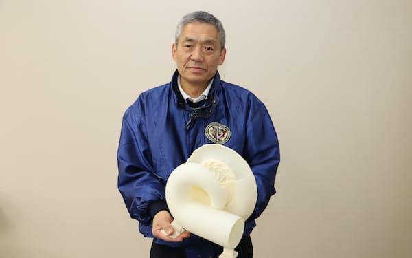 新型水車の模型を持つ東北小水力発電の和久礼次郎社長