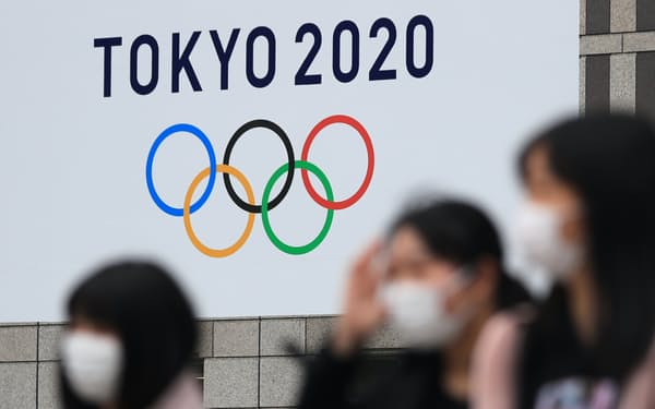 東京五輪の看板が掲げられた都庁前をマスク姿で歩く人たち(2020年3月)