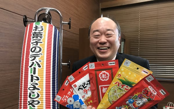 菓子のパッケージをあしらったマスクケースを広げる吉寿屋の神吉一寿社長。マスク3枚入りで1個300円(税別)