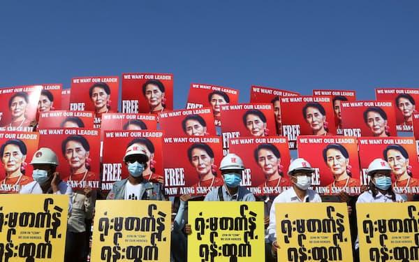 アウン・サン・スー・チー氏が描かれたプラカードを掲げて国軍に抗議するデモ隊=ロイター