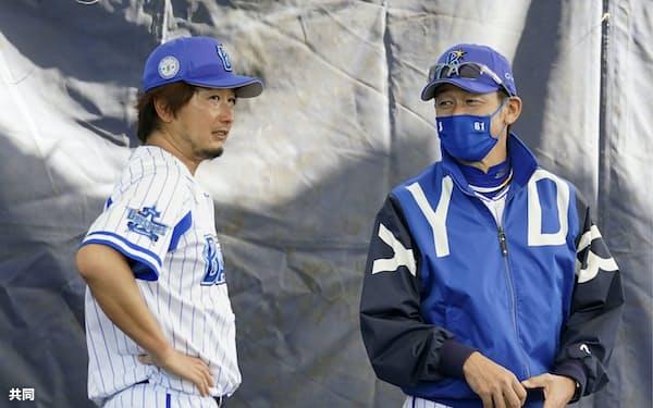 ブルペンでの投球練習を終えた三嶋(左)と話すDeNAの三浦監督=共同