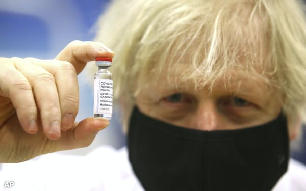 Britain's Prime Minister Boris Johnson holds a vial of the Oxford/Astra Zeneca Covid-19 vaccine at a vaccination centre in Cwmbran, south Wales, Wednesday Feb. 17, 2021. (Geoff Caddick/Pool via AP)