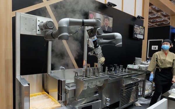 アームロボットが生麺をざるに入れる。ゆで上がると、水と冷水に通して麺をしめる