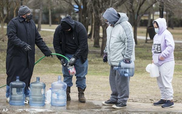 テキサス州の各地に開設された給水所では水を求める人が長い列をつくった=AP