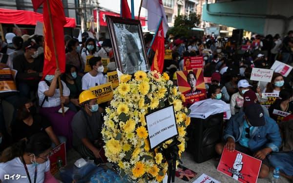 警察の銃撃で亡くなった女性を追悼する人々(20日、ヤンゴン)=ロイター