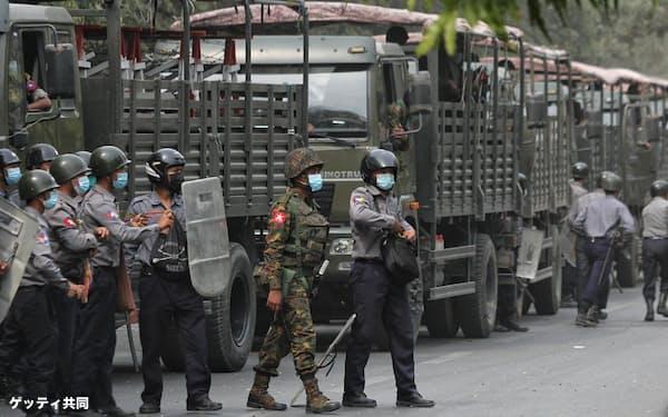 20日、ミャンマー・マンダレーでデモ隊の取り締まりに展開する治安部隊(ゲッティ=共同)