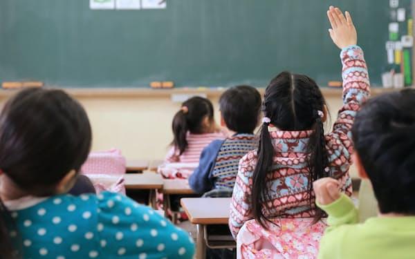 教室で手を上げる小学生(東京都江戸川区)