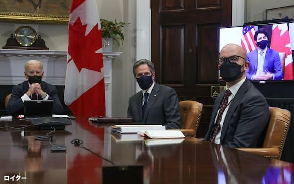 バイデン米大統領(左)はカナダのトルドー首相(右後方の映像)と会談した(23日、ホワイトハウス)=ロイター