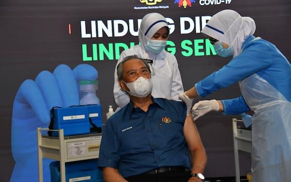 新型コロナのワクチンを接種されるマレーシアのムヒディン首相(24日、クアラルンプール近郊)=マレーシア政府提供
