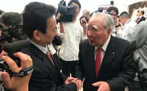 浜松市長選で4選を果たした鈴木康友氏と握手する鈴木修・スズキ会長(19年4月、浜松市内)