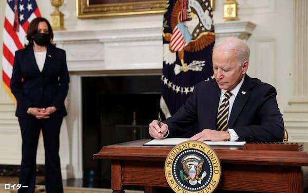 24日、米ホワイトハウスで大統領令に署名するバイデン氏(ワシントン)=ロイター