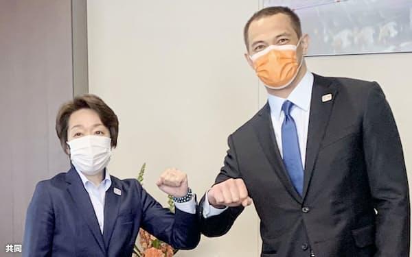スポーツ庁を訪問し、室伏長官(右)と腕を合わせる東京五輪・パラリンピック大会組織委の橋本会長(25日午後、東京・霞が関)=代表撮影