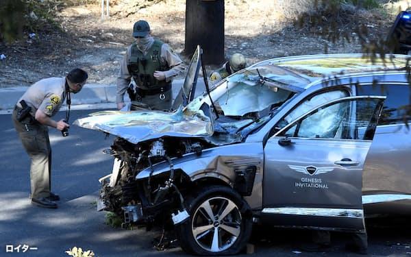 タイガー・ウッズ選手が運転していた自動車を調べるロサンゼルスの捜査担当者(23日)=ロイター