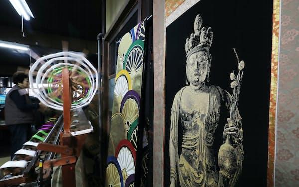 左の帯より多い約2万4400本のよこ糸を使い、聖林寺の十一面観音立像を織る=玉井良幸撮影