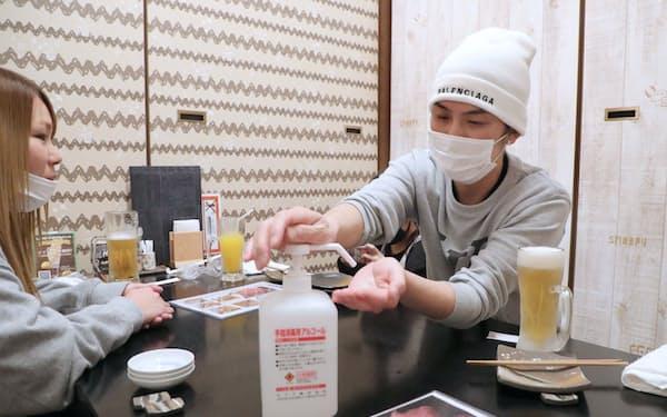 緊急事態宣言が解除され、営業再開した居酒屋で手指消毒する男性客(1日夕、堺市)