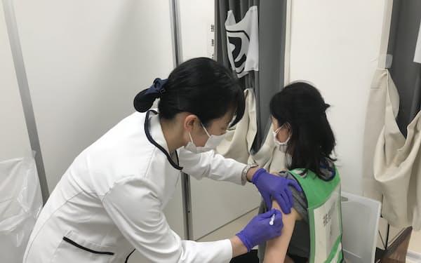 ワクチン接種訓練で被接種者の腕に注射する看護師(2月27日、さいたま市)