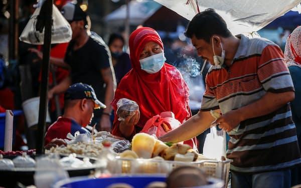 コロナ下でマスクをしながら市場を巡る人々のようす(インドネシア、ジャカルタ)=ロイター