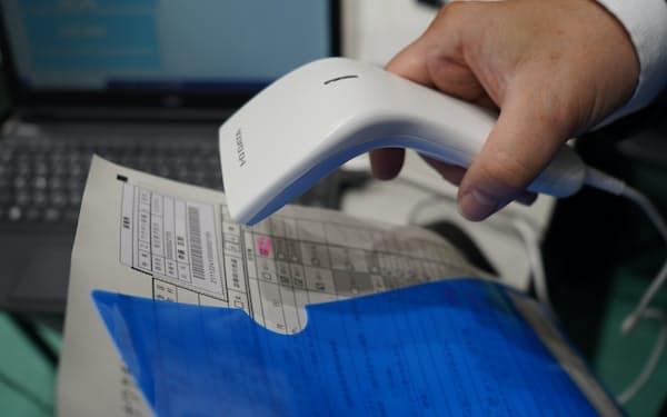 埼玉県戸田市が独自開発したワクチン接種記録システム。予診票に貼った接種券のバーコードを、接種後にリーダーで読み取る(撮影:日経クロステック)