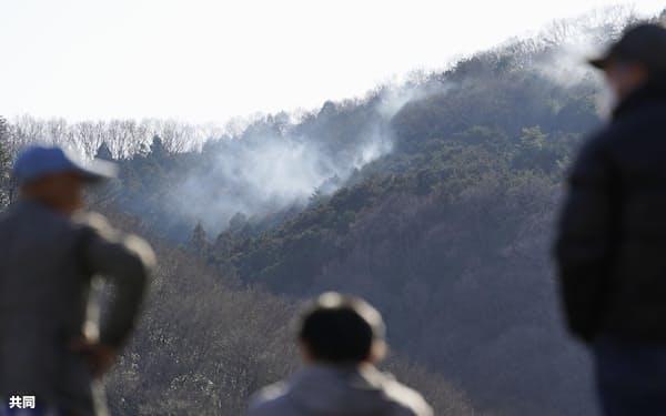 栃木県足利市の山林火災で、山から上る煙を見つめる人々(2月27日午後)=共同