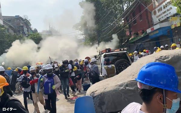 3日、ヤンゴンで、狙撃を避けるため煙幕を張る抗議デモの参加者ら=ロイター