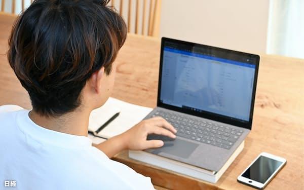 在宅勤務の定着はオンラインを通じた学び直しが広がる契機になりそうだ(自宅でパソコンに向かう会社員)