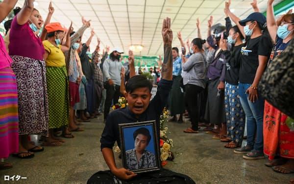5日、ミャンマー最大都市のヤンゴンで、治安当局によるデモ制圧の犠牲者の葬儀で抵抗のポーズをとる市民ら=ロイター