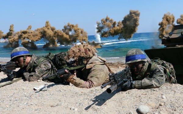 水陸両用装甲車で上陸後に銃を構える韓国軍の兵士ら=16年の演習