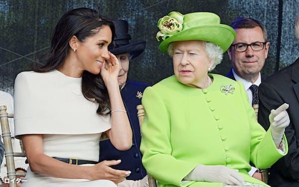 メーガン妃(左)と話すエリザベス女王(2018年6月、英中部ランコーン)=ロイター