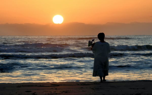 朝日に照らされる福島県いわき市の海岸。花束を持った女性が海に向かって祈っていた