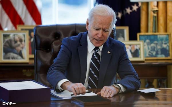 米国では給付金などの恩恵を受けた中低所得層が貯蓄を殖やしている(11日、新型コロナウイルス経済対策法案に署名したバイデン大統領)=ロイター