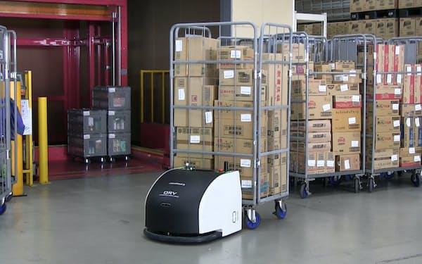 オカムラが開発した搬送ロボットが商品を載せたカゴつき台車を運ぶ(群馬県前橋市の物流拠点)