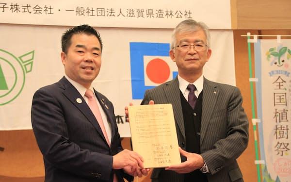 カーボンオフセットで連携協定を結んだ日本電気硝子の松本元春社長(右)と滋賀県の三日月大造知事(16日、滋賀県庁)
